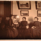 Сестры Николаи в гостиной усадебного дома; Мария Николаевна (сидит на диване в центре), Александра Николаевна (справа); у их ног сидит Софья Николаевна.
